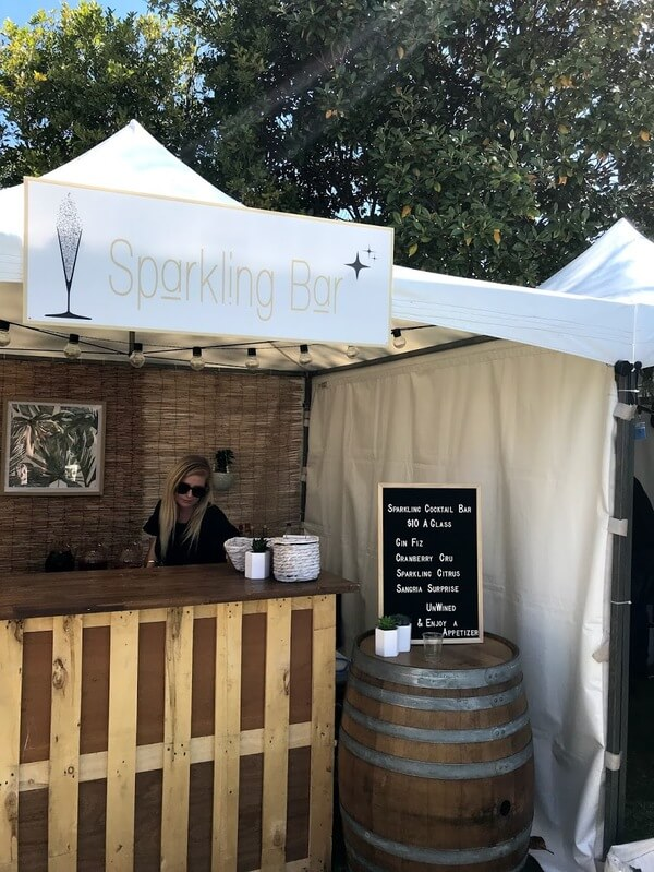 sparkling-cocktail-bar-with-woman-in-black-shirt-and-sign-on-a-wine-barrel