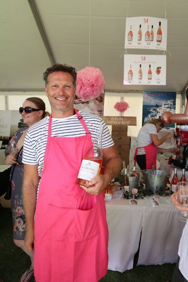man wearing a pink apron holding a bottle of rose