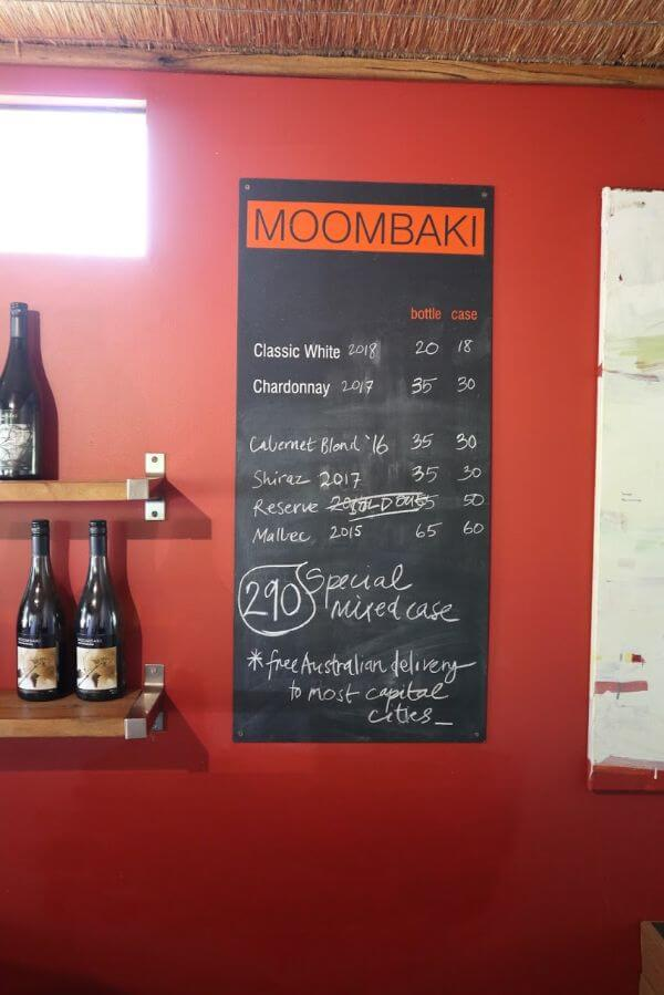 moombaki sign on a red wall with wine prices