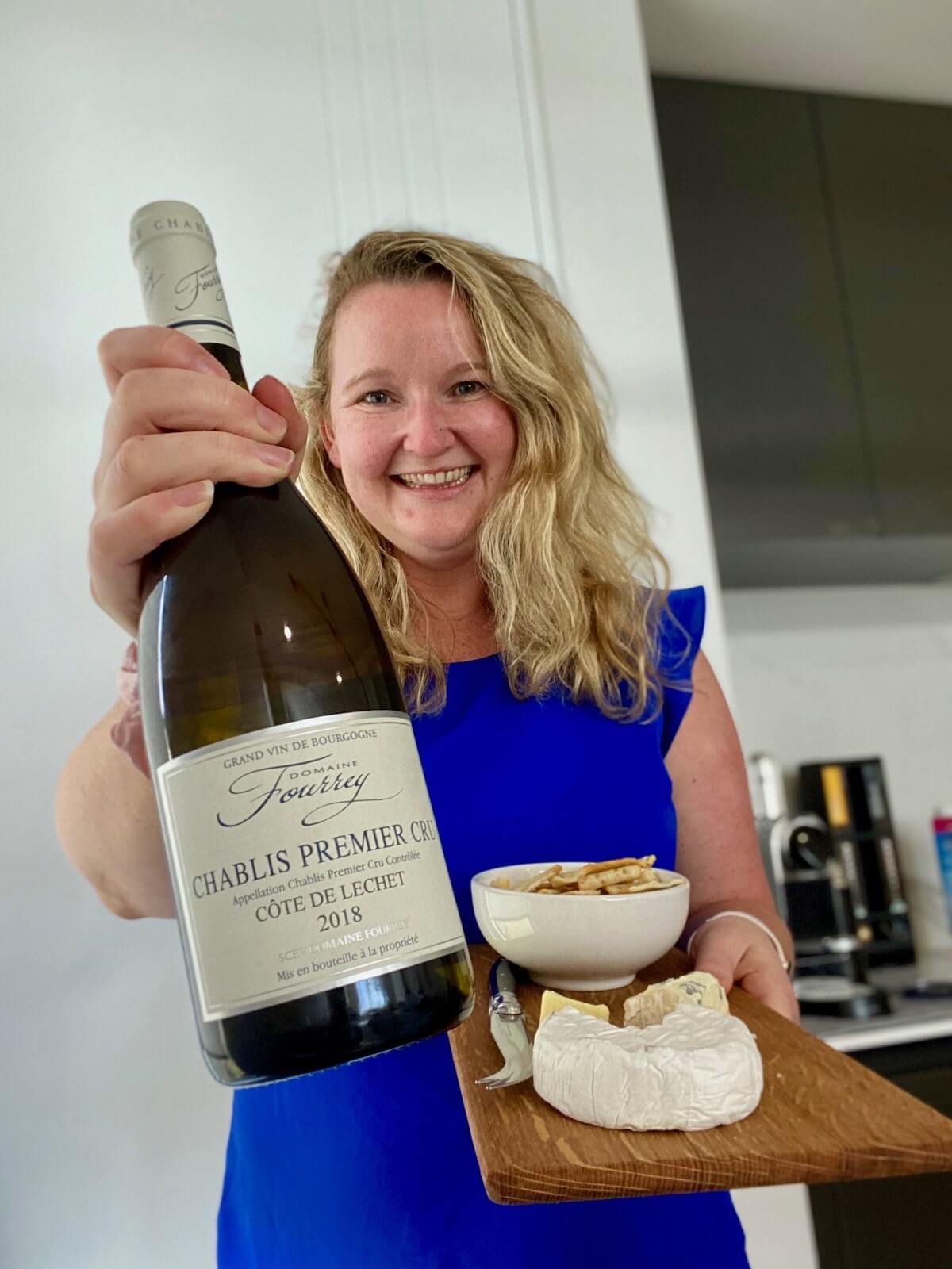 Wine blogger Casey holding a bottle of Domaine Fourrey Premier Cru Chablis from Popsy and JJ and a cheese platter